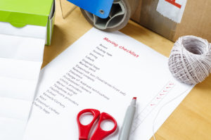 A house moving checklist on a table, surrounded by labels, packaging tape roller, scissors, red marker pen, a ball of string and a sealed box. Some of the checkboxes have been ticked in red.; Shutterstock ID 143660524